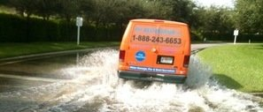 Water Damage Restoration Van Driving Down Flooded Street